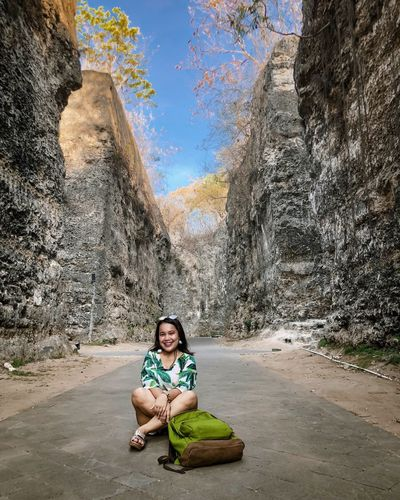 Portrait of smiling young woman sitting on road against rock formations