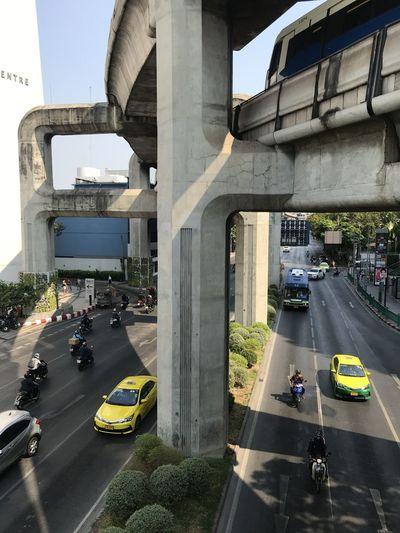 Vehicles on road against bridge in city