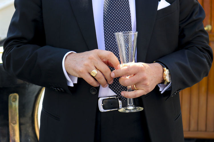 Midsection of well-dressed man holding drinking glass