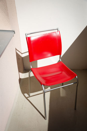 Red Chair Seat No People Absence Wall - Building Feature Empty Shadow Still Life Furniture White Color Box Flooring High Angle View Sunlight Architecture Day Container Outdoors Balcony Single Object Sunlight And Shadow Living Lifestyle Simple