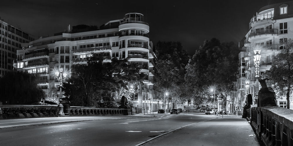 Road by illuminated buildings against sky at night
