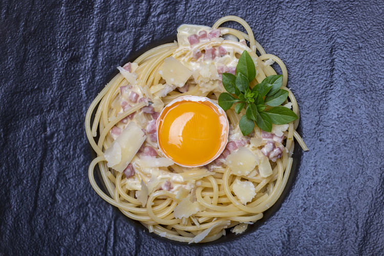 High angle view of spaghetti and egg yolk served on slate