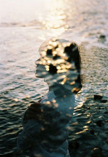 Double exposure of woman and sea