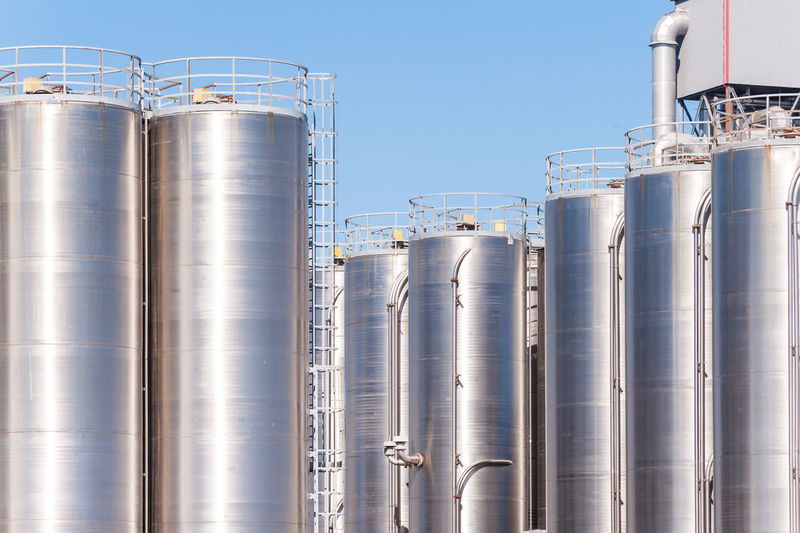 Silos in factory against sky