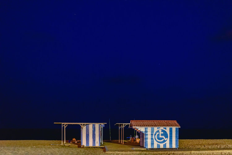 Hooded beach chairs against clear blue sky at night
