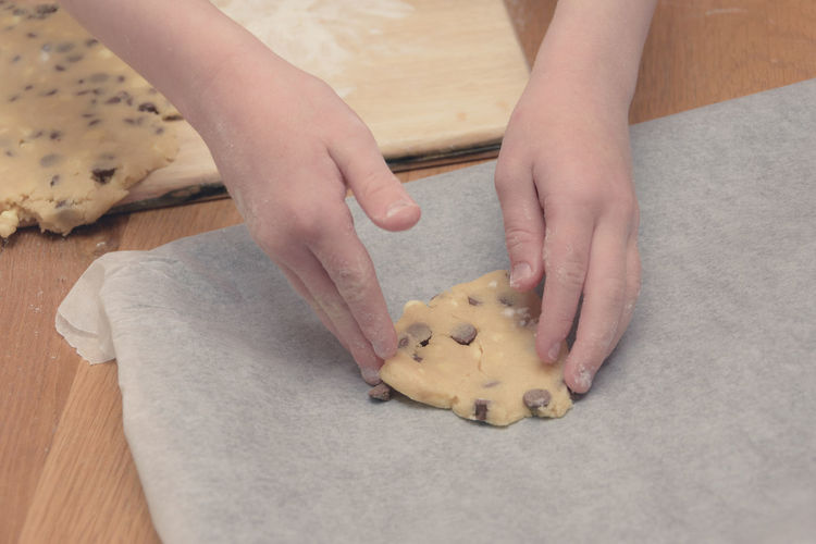 Cropped hands of woman making cookies on table