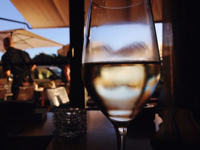 Close-up of white wine glass on table at restaurant