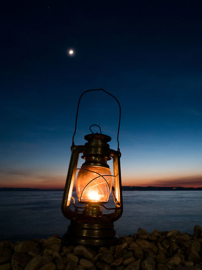 Fuel lantern on the beach close to the sea and moon on the blue sky above Beach Blue Close-up Dark Flame Glowing Illuminated Lamp Lantern Light Lighting Lighting Equipment Moon Nature Night No People Oil Lamp Old Outdoors Retro Scenics Sea Sky Vintage Water