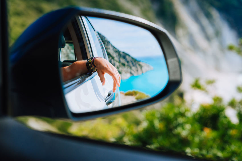 Tanned female hand in the car side view mirror. Blue mediterranean sea and white rocks landscape in background Mirrored Relaxing Car Close-up Day Finger Glass - Material Hand Human Body Part Human Hand Land Vehicle Leisure Activity Lifestyles Mirror Mode Of Transportation Motor Vehicle One Person Outdoors Photography Themes Real People Reflection Road Trip Selective Focus Side-view Mirror Transportation