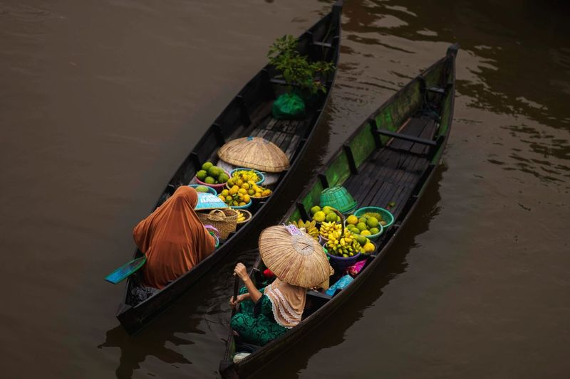 People selling fruits in boats on canal