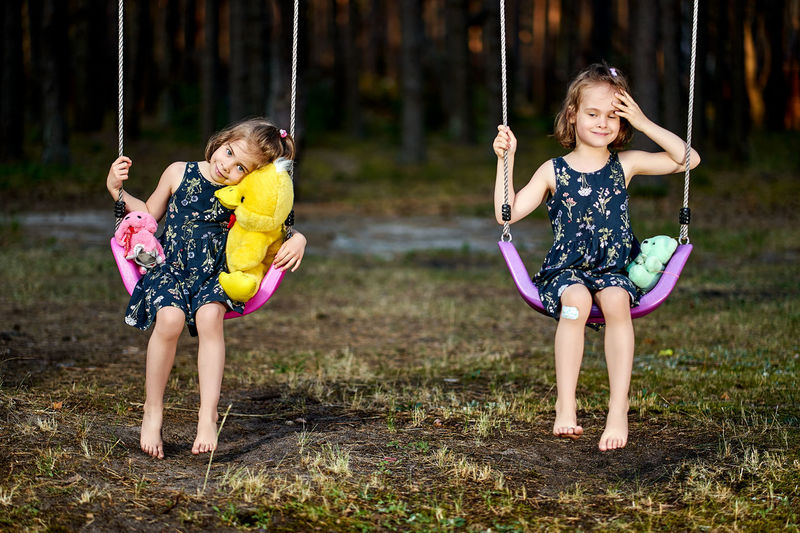 Portrait of cute girls sitting on swing at park