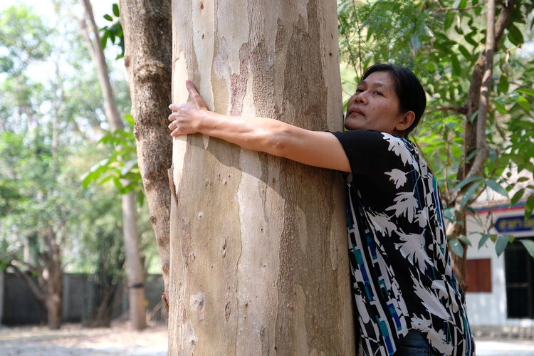 Nature Real People Women Tree Day Standing Outdoors Smiling Plant Tree Trunk Adult Side View Trunk Lifestyles Young Adult One Person Floral Pattern Casual Clothing Leisure Activity Focus On Foreground Human Arm
