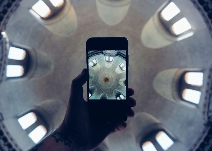 Cropped hand photographing ceiling through smart phone