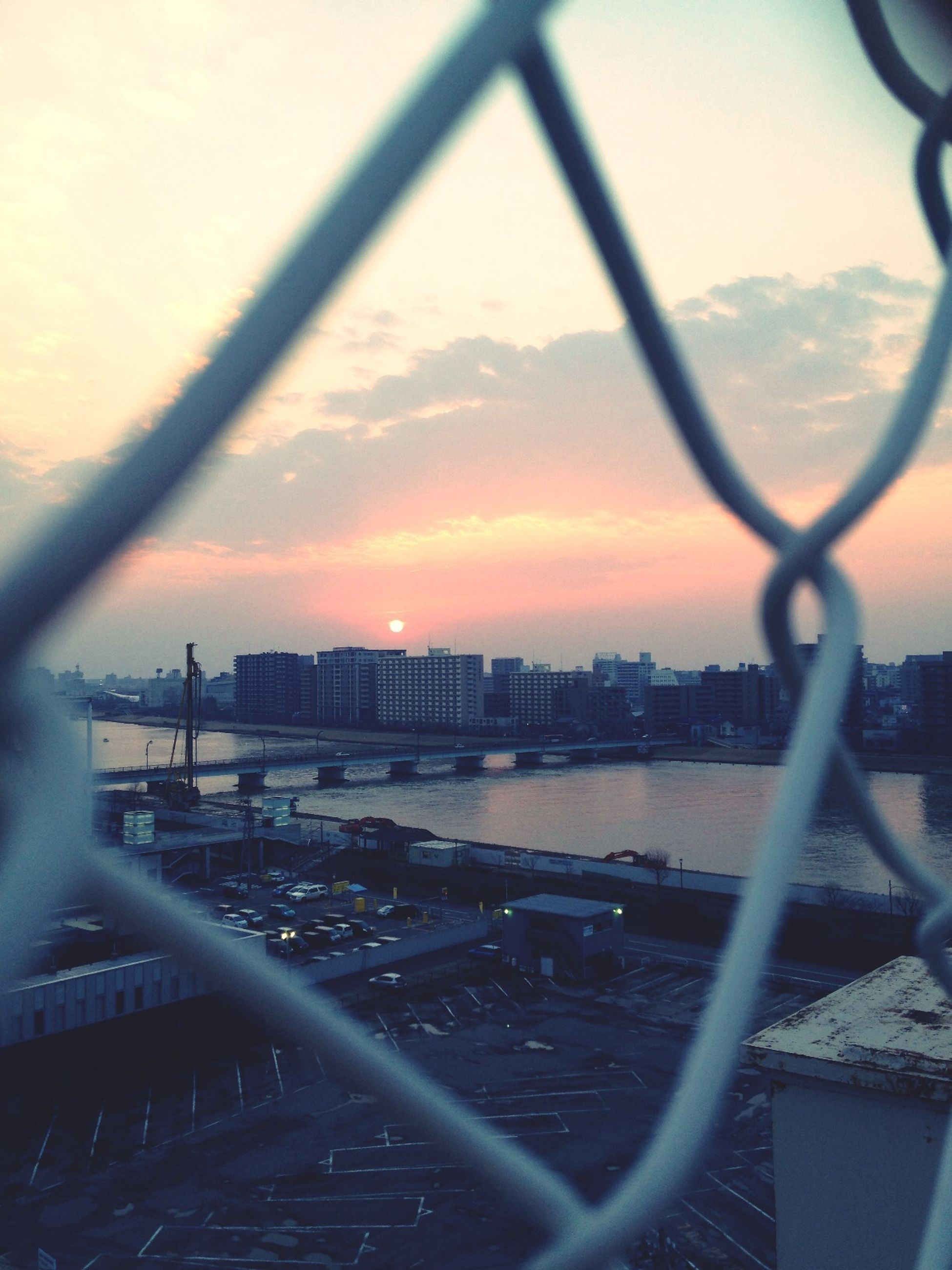 water, sunset, sky, built structure, architecture, chainlink fence, metal, river, railing, fence, sea, building exterior, city, safety, orange color, protection, cloud - sky, nature, cityscape, no people
