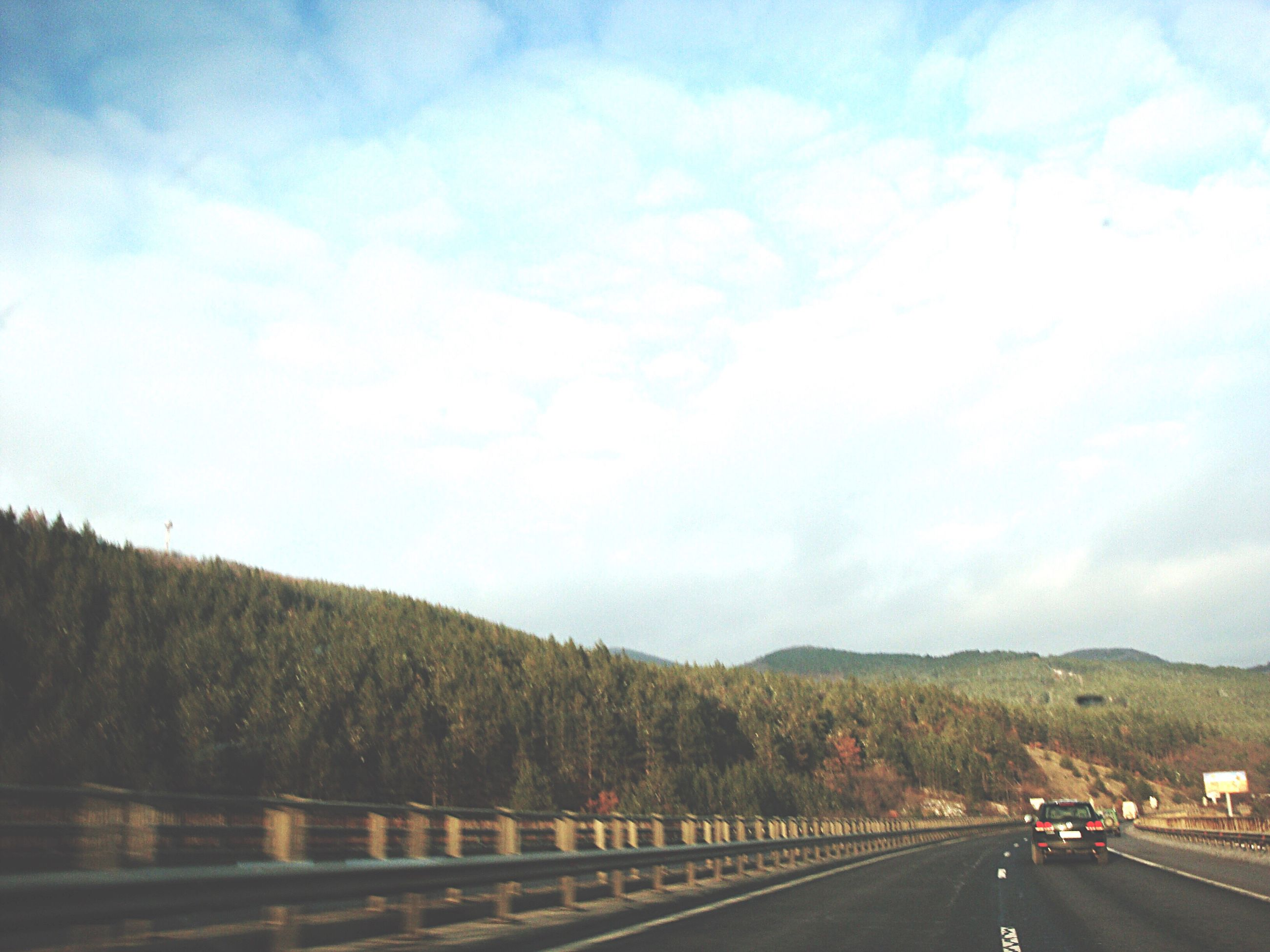 road, mountain, sky, the way forward, cloud - sky, road marking, mountain range, cloud, cloudy, landscape, scenics, country road, nature, tranquility, tranquil scene, diminishing perspective, beauty in nature, outdoors, vanishing point, day, no people, non-urban scene, empty, remote, blue, travel destinations, idyllic