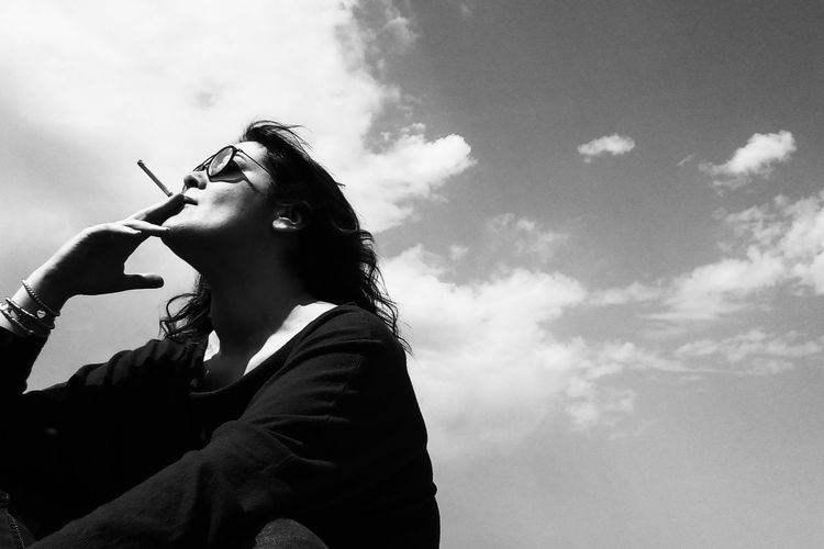 Low angle view of woman smoking cigarette while sitting against sky