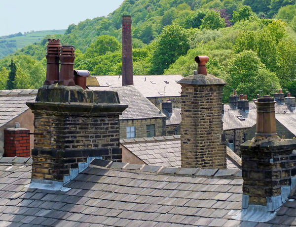 chimneys and roofs of traditional stone build houses and mills typical of west yorkshire small towns and villages set against steep valley woodland with blue summer sky Chimneys Yorkshire Architecture Building Building Exterior Built Structure Day History House Nature No People Old Outdoors Plant Residential District Roof Roof Tile Stone The Past Travel Destinations Tree Village Village Life