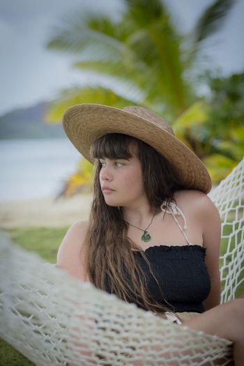 Woman looking away while sitting in hammock