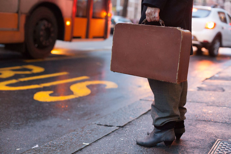 Low section of businessman carrying suitcase while standing on city street