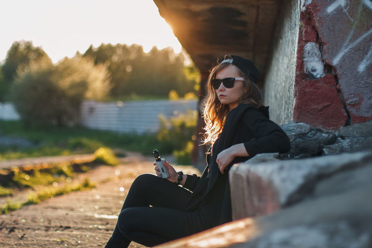 Young Woman Sitting In Sunglasses Against Sky During Sunset