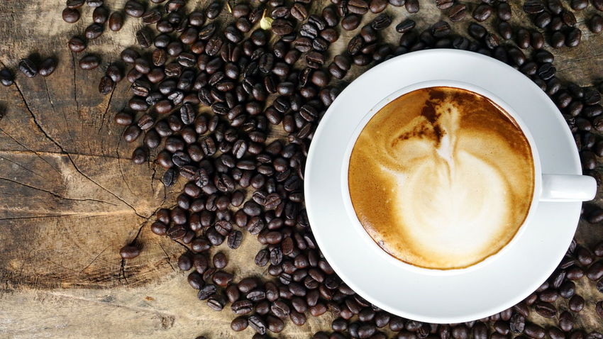A cup of latte, cappuccino or espresso coffee with milk put on a wood table with dark roasted coffee beans Aroma Bakery Beans Boiler Cafe Cappuccino Coffee Cookies Cream Cup Drink Espresso Fresh Headshot Latte Make Mashed Milk Morning Plate Pressure Roasted Robust Stream Table