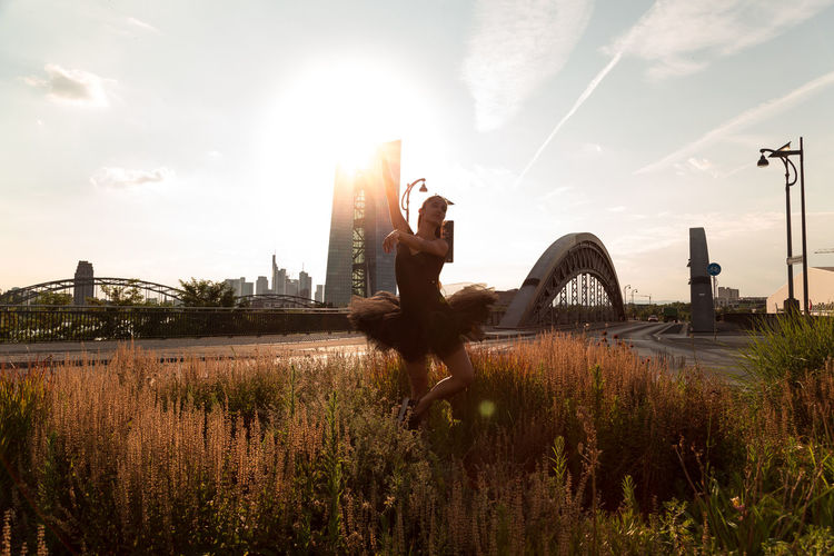 Woman dancing on field in city against sky during sunset