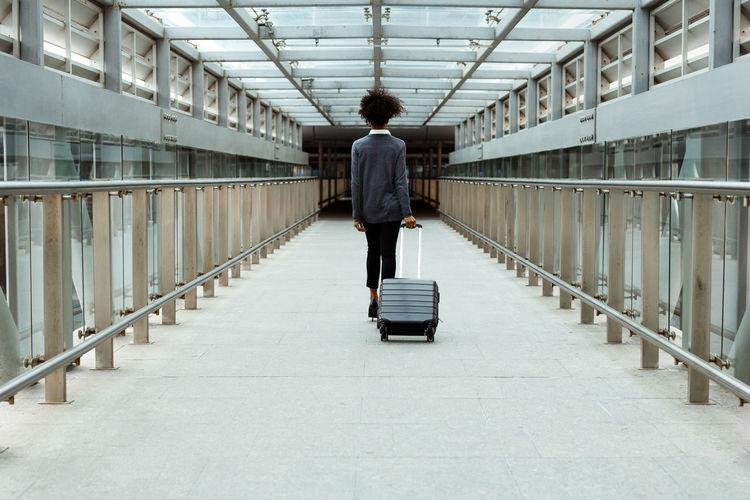 Rear view of woman walking at airport