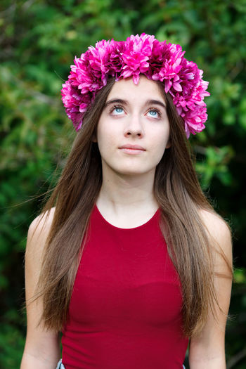 Portrait of beautiful young woman with pink flower