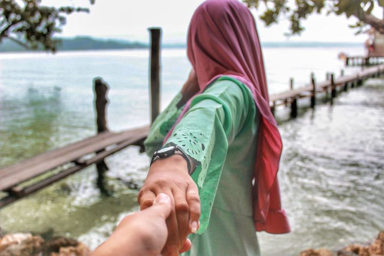 Cropped image of man holding woman hand by lake