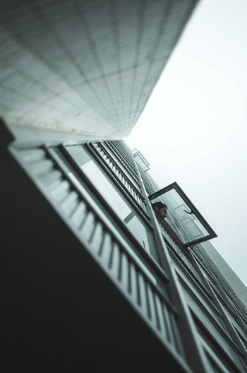 Low angle view of man peeking through window from building against clear sky