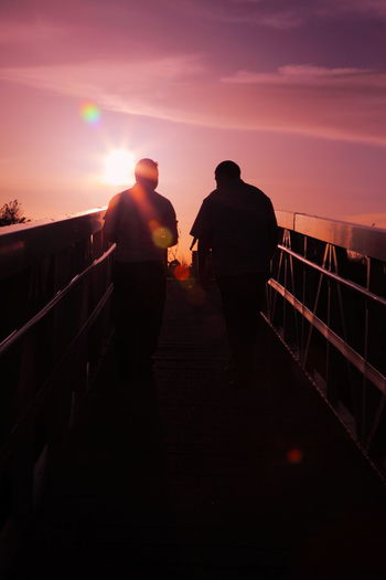 Rear View Of Silhouette Friends Walking On Footbridge At Sunset