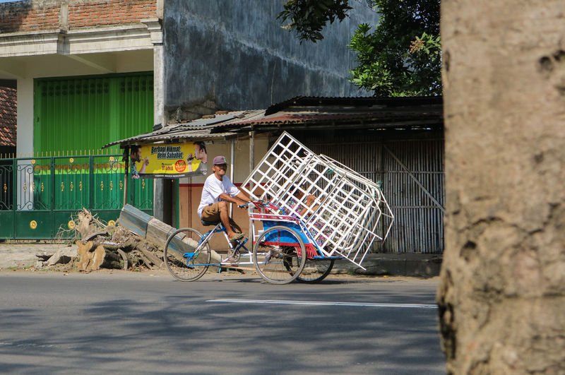 Man riding tricycle against houses
