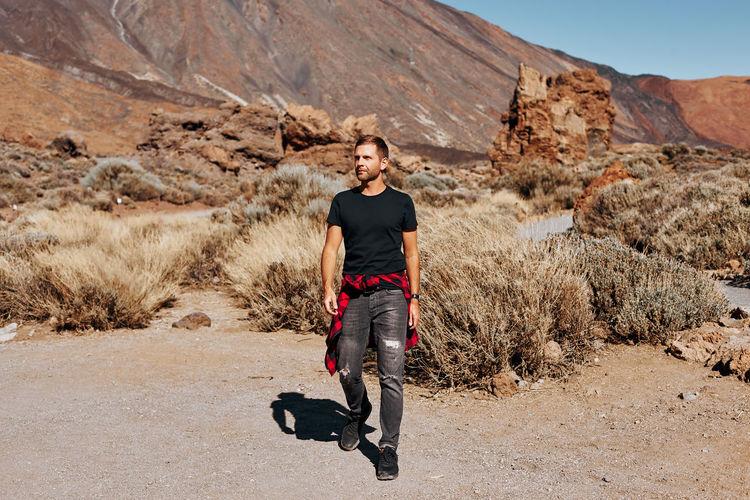 Full length of man walking on land against mountain