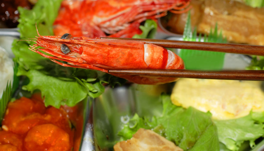 Detail of chopsticks holding a shrimp on a seafood assortments tray. Food Food And Drink Freshness Healthy Eating Seafood Ready-to-eat Close-up Vegetable Still Life Crustacean Red Salad Selective Focus Serving Size Meat Focus On Foreground Shrimp Shrimp - Seafood Chopsticks Chopsticks With Shrimp