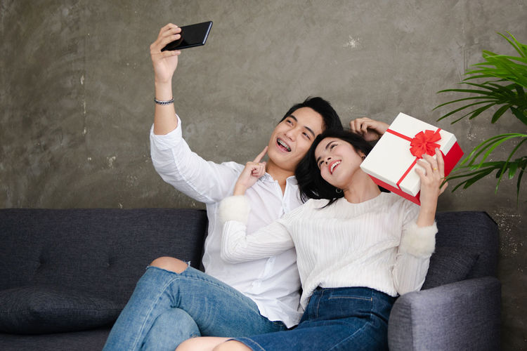 Beautiful young couple is holding gift box,doing selfie and smiling while celebrating at home Two People Emotion Technology Young Women Young Men Positive Emotion Young Adult Togetherness Sitting Casual Clothing Women Couple - Relationship Happiness Selfie Heterosexual Couple Smiling Mobile Phone Young Couple Wireless Technology Boyfriend Girlfriend Gift Box Gift Leisure Activity Love