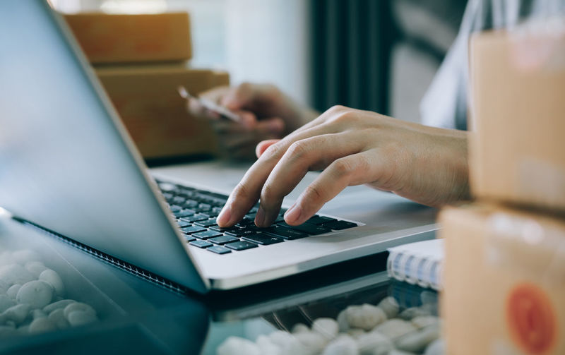 Midsection of man using laptop amidst boxes on table