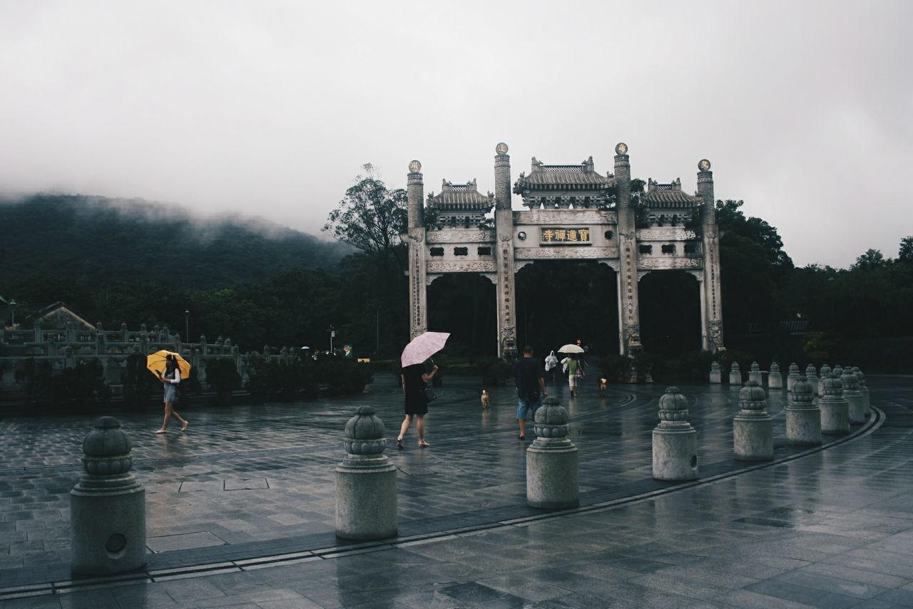 People passing through gate at ngong ping village during rainy season