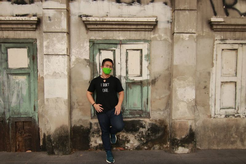 Full length portrait of young man wearing pollution mask standing by window
