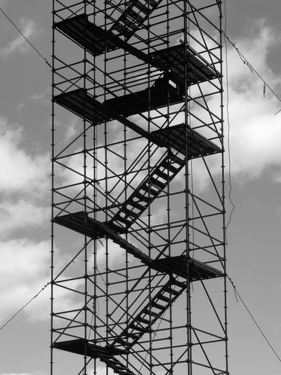 A portion of a staircase and scaffolding, at the site of an interstate highway bridge replacement in Brattleboro, VT. Cable Cloud Cloud - Sky Construction Site Geometric Shapes No People Outdoors Scaffold Scaffolding Sky Staircase Stairs Tall - High