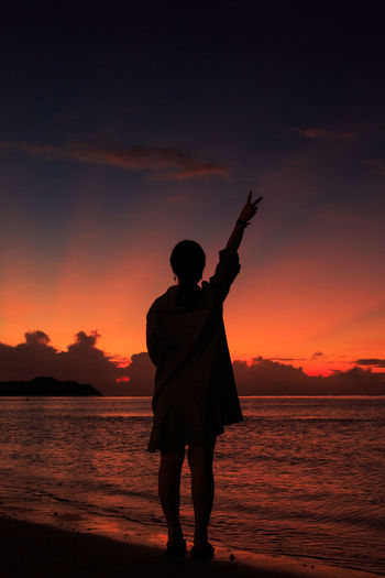 Silhouette woman with hand raised standing at beach against orange sky