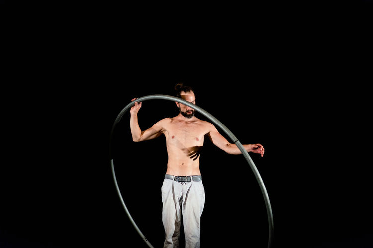 Circus Adult Arms Raised Black Background Casual Clothing Copy Space Front View Hairstyle Holding Human Arm Indoors  Men Mid Adult One Person Performance Plastic Hoop Shirtless Skill  Standing Studio Shot Three Quarter Length Young Adult