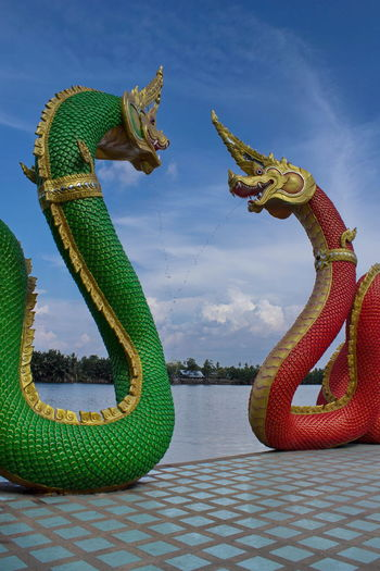 Chinese Dragon Statues By River Against Sky