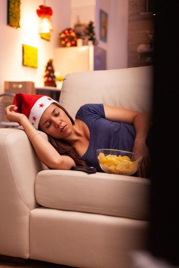 Young woman lying on sofa at home
