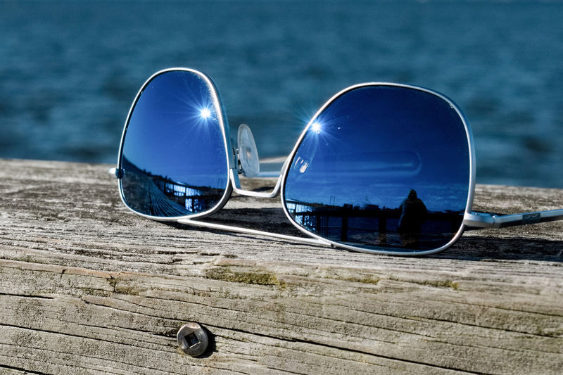 Close-up of sunglasses on beach against sky
