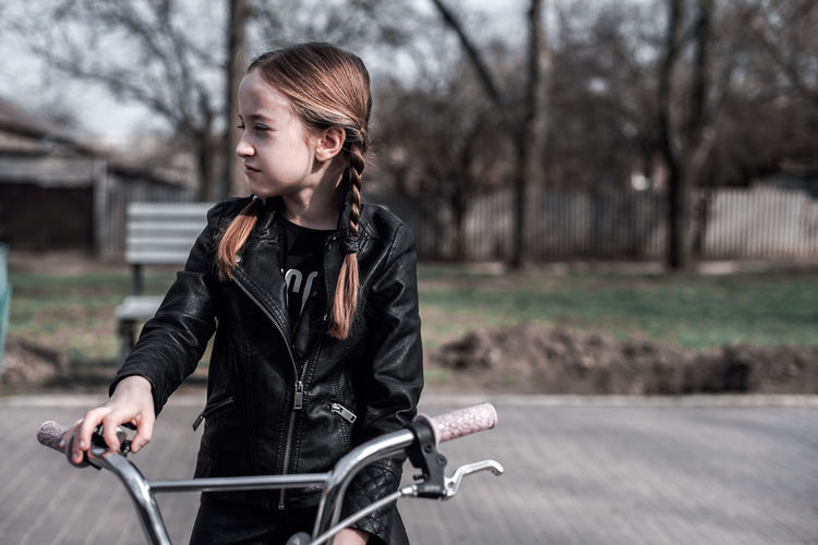 Smiling girl with bicycle at park