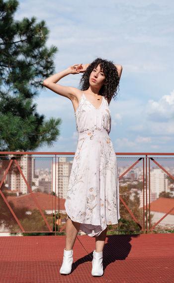 Portrait of woman standing on floor against sky