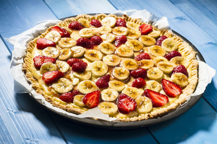 High angle view of strawberry banana tart served in plate on table
