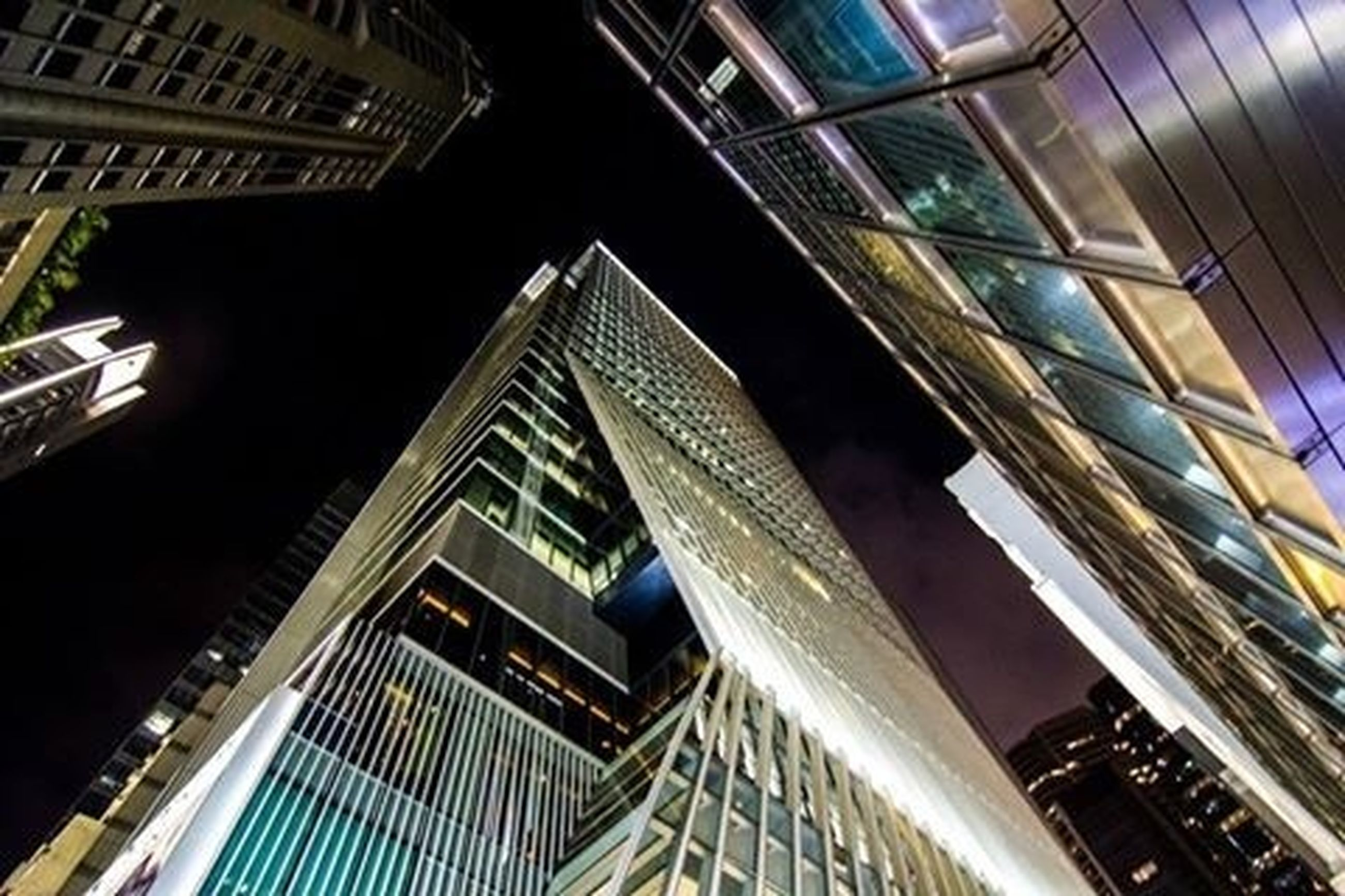 architecture, low angle view, built structure, building exterior, building, illuminated, night, window, modern, city, residential building, office building, residential structure, glass - material, no people, skyscraper, outdoors, reflection, tall - high
