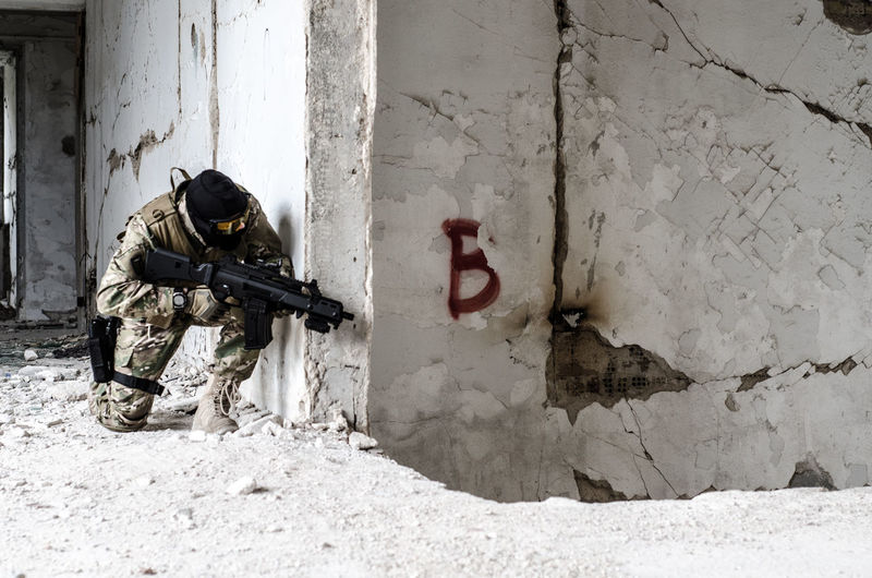 Full Length Of Army Soldier With Gun By Graffiti On Wall