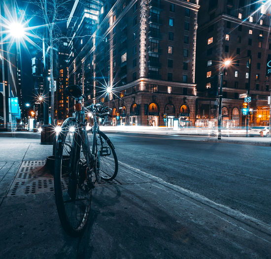 Bicycles on city street by buildings at night